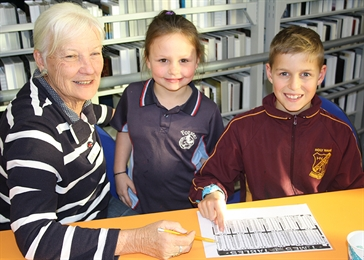 Homework Help Tutor, Lesley Guiney working with Shaneika Wright and Nash Bowen at Forster Library.